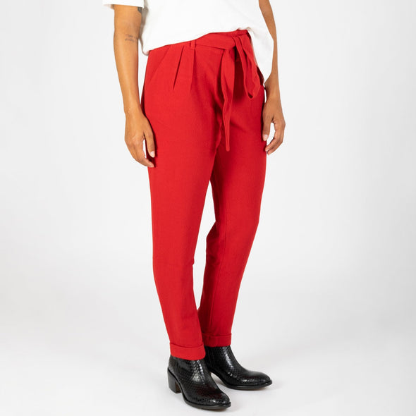 Red high waisted trousers with a belt.
