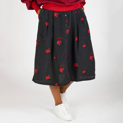 Midi skirt with white dots and red flowers print on a black background.