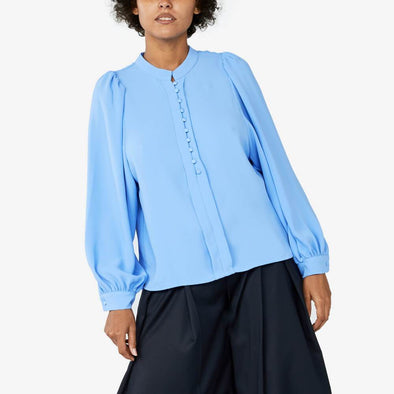 Longsleeve fitted cuff blouse with little ruffles on the shoulder featuring back cut with big pleat.