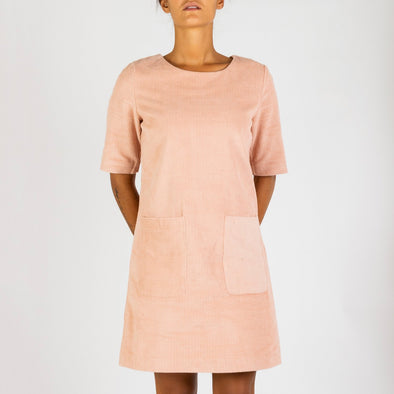 Light pink corduroy straight dress with short sleeves, round neck and double patch pockets at the thighs.