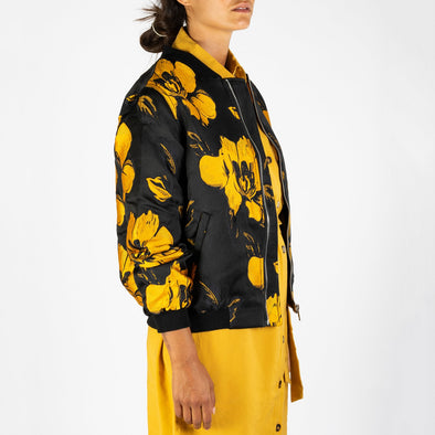Black bomber jacket with a yellow flower print.