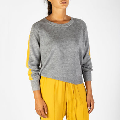 Loose gryy sweater with a mustard band on the sleeves.