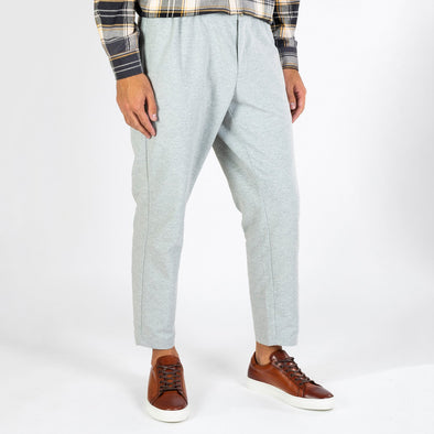 Grey loose fit pants with an elastic string at the waist.