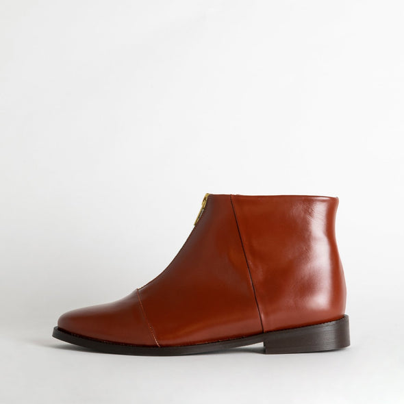 Brown zipper flat boots in full-grain leather.