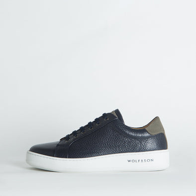 Low-top minimalist sneakers in navy blue leather and grey suede panels.