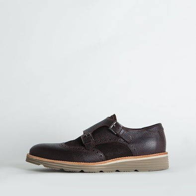 Double monk strap shoes in dark brown leather with brogue details.