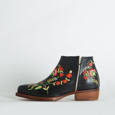 Black flat ankle boots with colorful floral details.