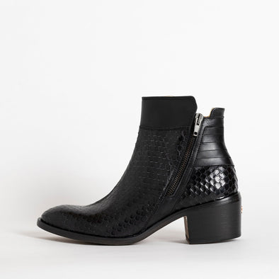 Heeled ankle boots in black leather with texture detailing.