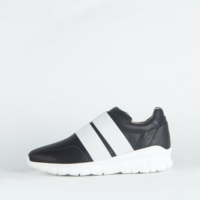 Minimalist black sporty runners with two precise straps harmoniously overlapping the simplicity of the its shape.