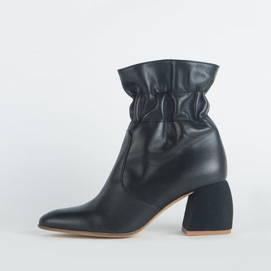 Black leather boots with wrinkled ankle and distinct heel shape.