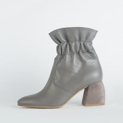 Grey leather boots with wrinkled ankle and distinct heel shape.