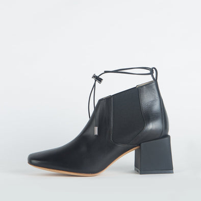 Black leather ankle boots with a thin ankle strap and distinct heel shape.