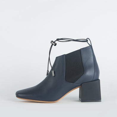 Navy blue leather ankle boots with a thin ankle strap and distinct heel shape.
