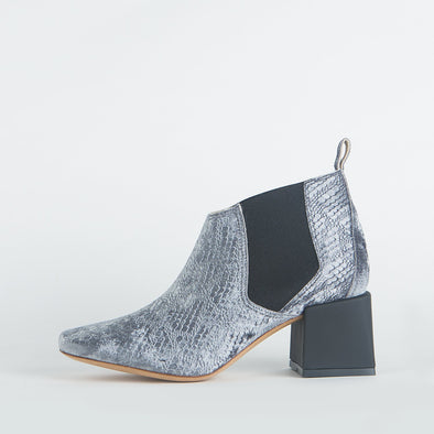 Silver patterned ankle boots with a thin ankle strap and distinct heel shape.