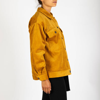 A mustard colored statement A/W piece  which includes large front patch pockets with horn buttons.