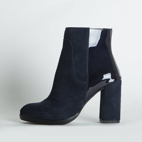 Black suede heeled ankle boots with varnish detailing.