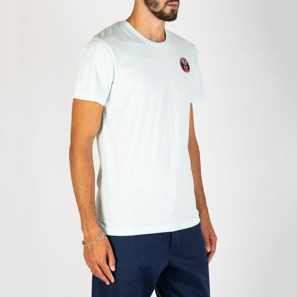 Basic white t-shirt with a patch on the chest.