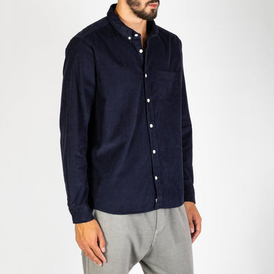A casual, long sleeved navy blue corduroy shirt.
