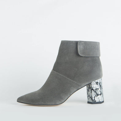 Grey suede pointed toe ankle boots with a patterned geometric heel.
