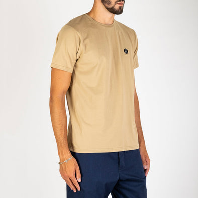 "Khaki t-shirt with the brand's ""Essential"" patch on the chest."