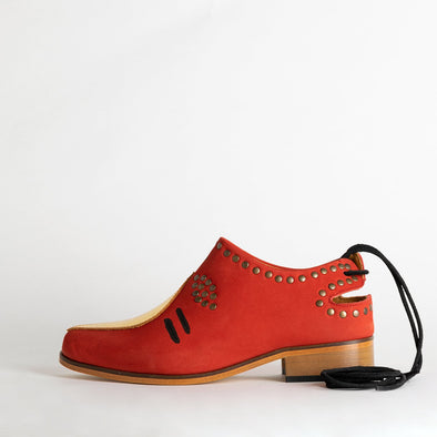 Red leather shoes with golden details in leather and bronze rivets.