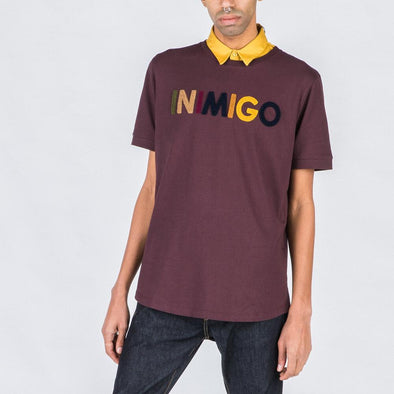 Burgundy t-shirt with multicolored brand stamp.
