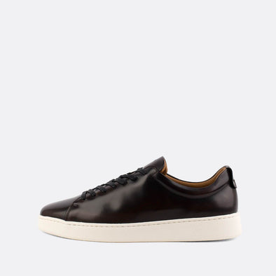 Black polished leather low-top sneakers.