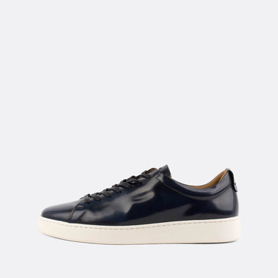 Navy blue polished leather low-top sneakers.