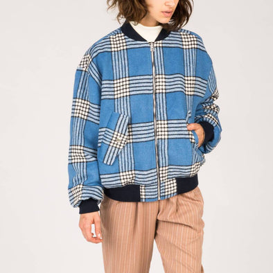 Reversible bomber jacket with blue check print on one side and beige and golden on the other.