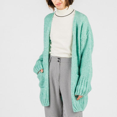 Pistachio cardigan with long puffy sleeves and two side pockets.
