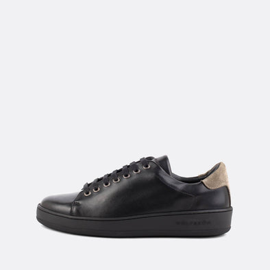 Casual black leather low-top sneakers with taupe panels.