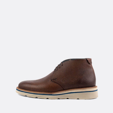 Brown leather chukka boots with blue details.