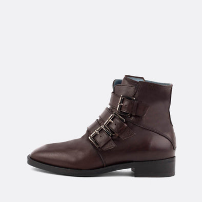 Brown leather flat ankle boots with three straps and silver buckles.