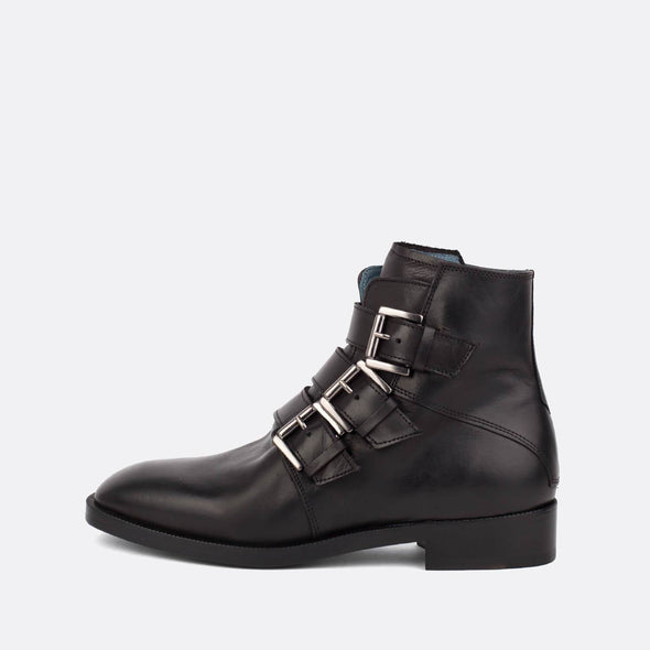 Black leather flat ankle boots with three straps and silver buckles.