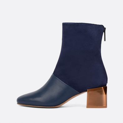 Heeled ankle boots in oxford blue leather and suede with golden heel.