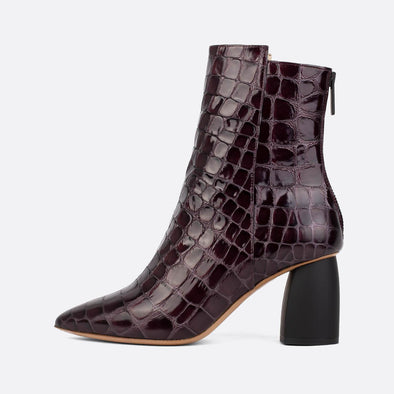 Heeled ankle boots in bordeaux croc embossed leather.