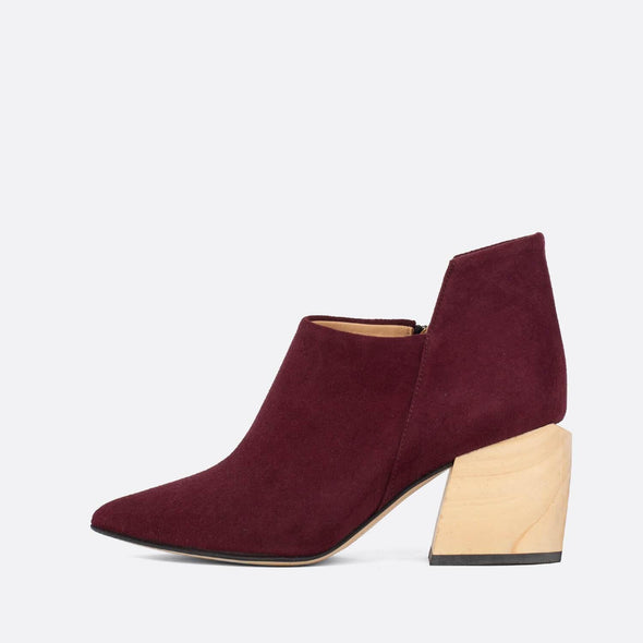 Pointed-toe bordeaux suede ankle boots with geometric cut and wooden block heel.