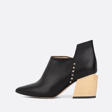 Pointed-toe black leather ankle boots with geometric cut and wooden block heel.