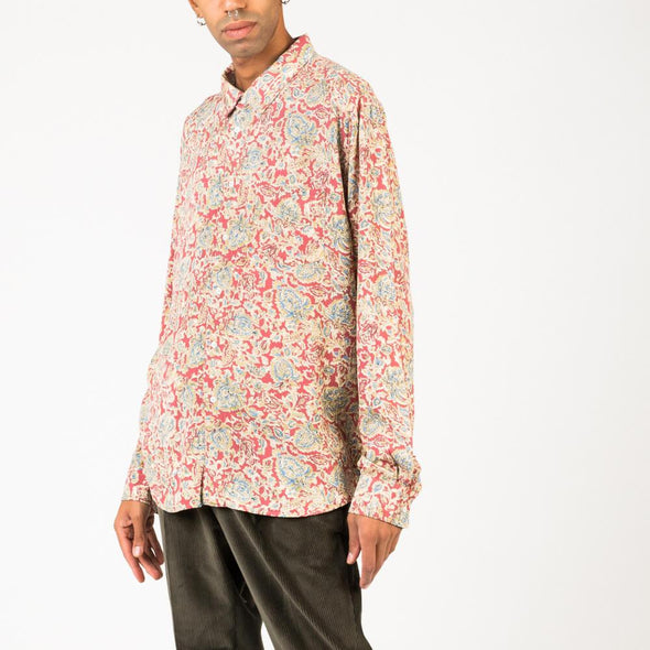 Long sleeved shirt with floral print in shades of red, yellow and blue.