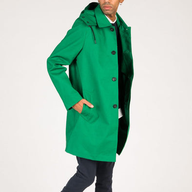 Green timeless raincoat with piped front pockets and removable hood.