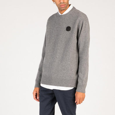 Grey plain knit jumper with black dot patch detail around the left side of the chest.