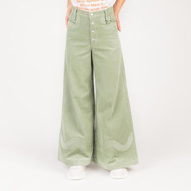 Forest green wide leg corduroy trousers with gold buttons.