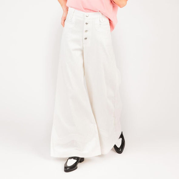 White wide leg corduroy trousers with gold buttons.