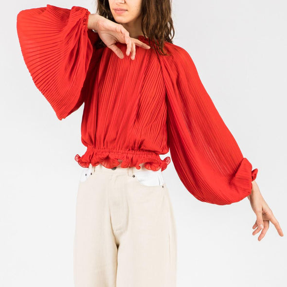Cropped relaxed fit top with balloon sleeves and ruffle details.