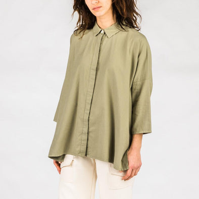 Olive green oversized organic cotton shirt with lapel collar, hidden front buttons and 3/4 sleeves.