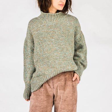 Grey turtleneck sweater made from recycled fibers.