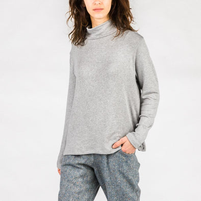 Grey turtleneck with long sleeves and relaxed shoulders.