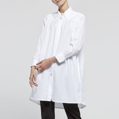 Long white shirt-dress with an outspokenly feminine cut and lavish details.