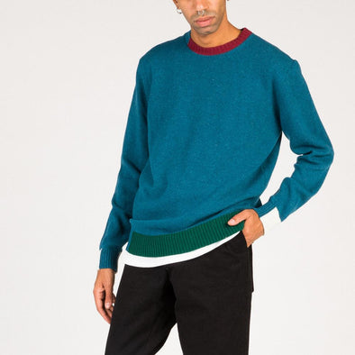 Color blocked knit in petrol blue with red, white and green details.
