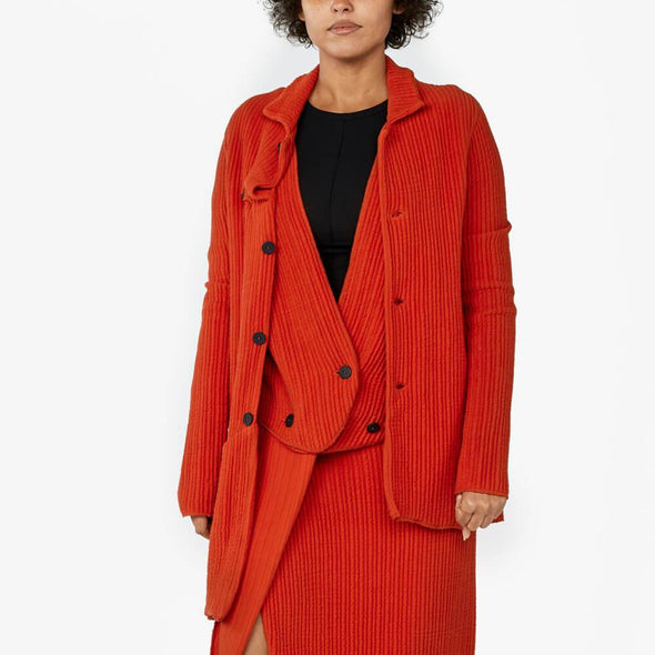 Red jacket with irregular front button fastening with one front pocket and an asymmetrical hemline.